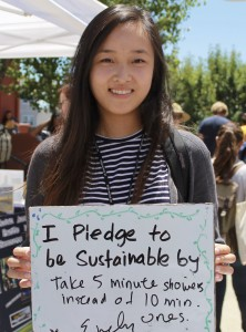 Student holds up a whiteboard with a pledge to take shorter showers
